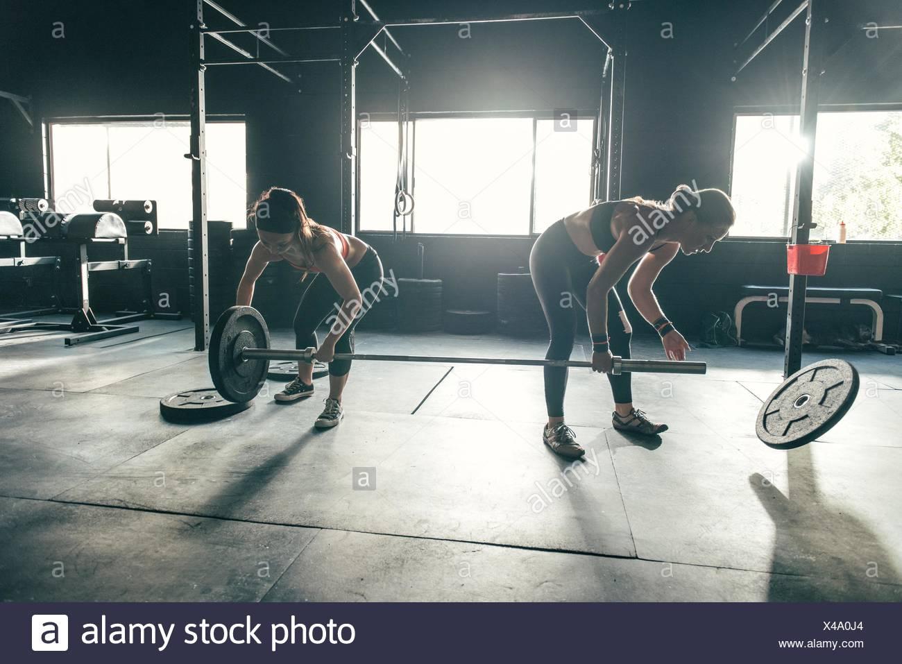 Women preparing barbell in gym - Stock Image