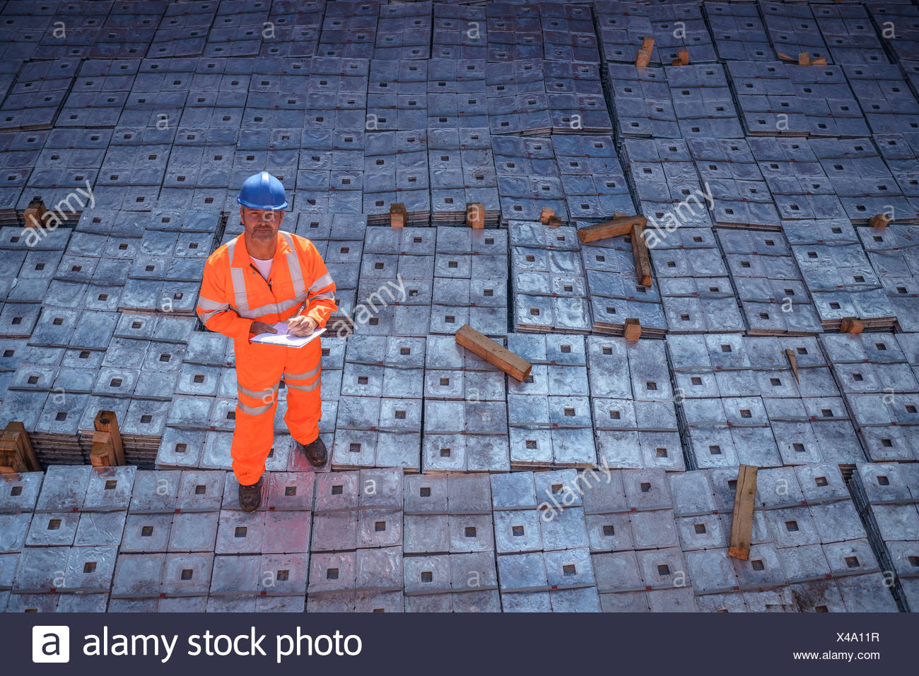 Worker in reflective workwear standing on metal alloy cargo in ship's hold, portrait - Stock Image