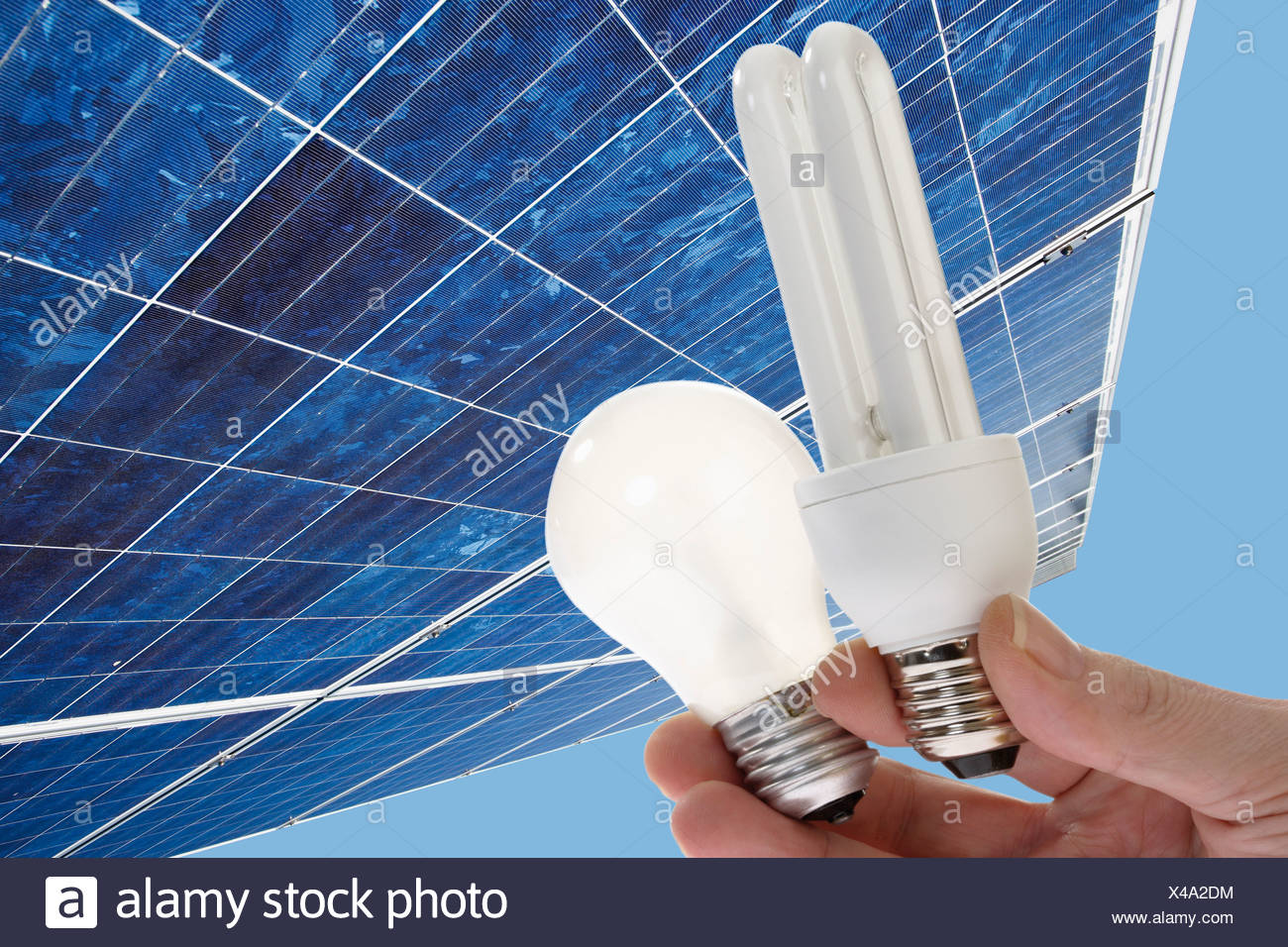 Human hand holding energy saving light, bulb against  solar panel, close up. - Stock Image