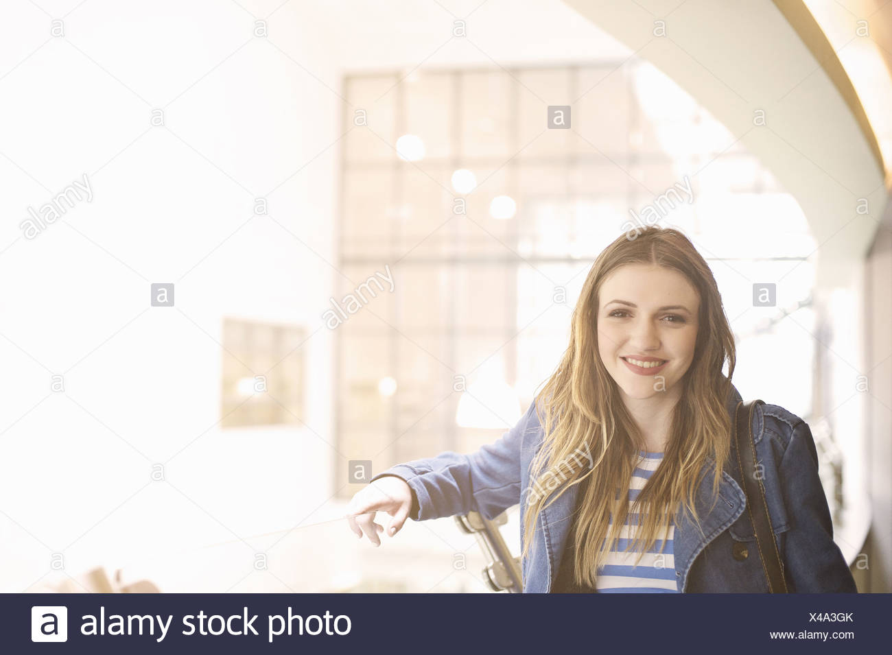 Young woman wearing denim jacket looking at camera - Stock Image