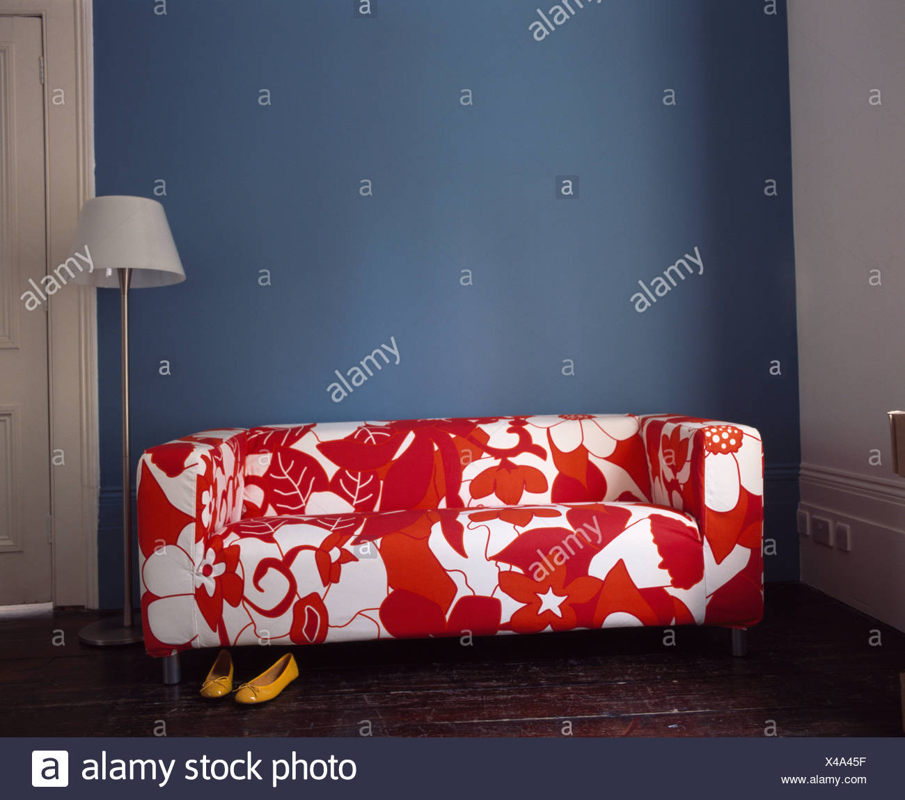 Close-up of modern red+white stylized floral-patterned sofa - Stock Image