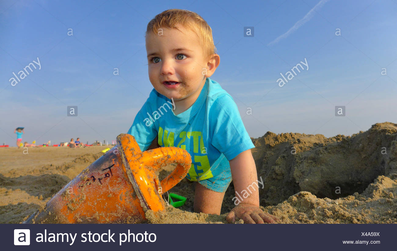 little boy wearing a T-shirt playing on a sandy beach, Netherlands - Stock Image