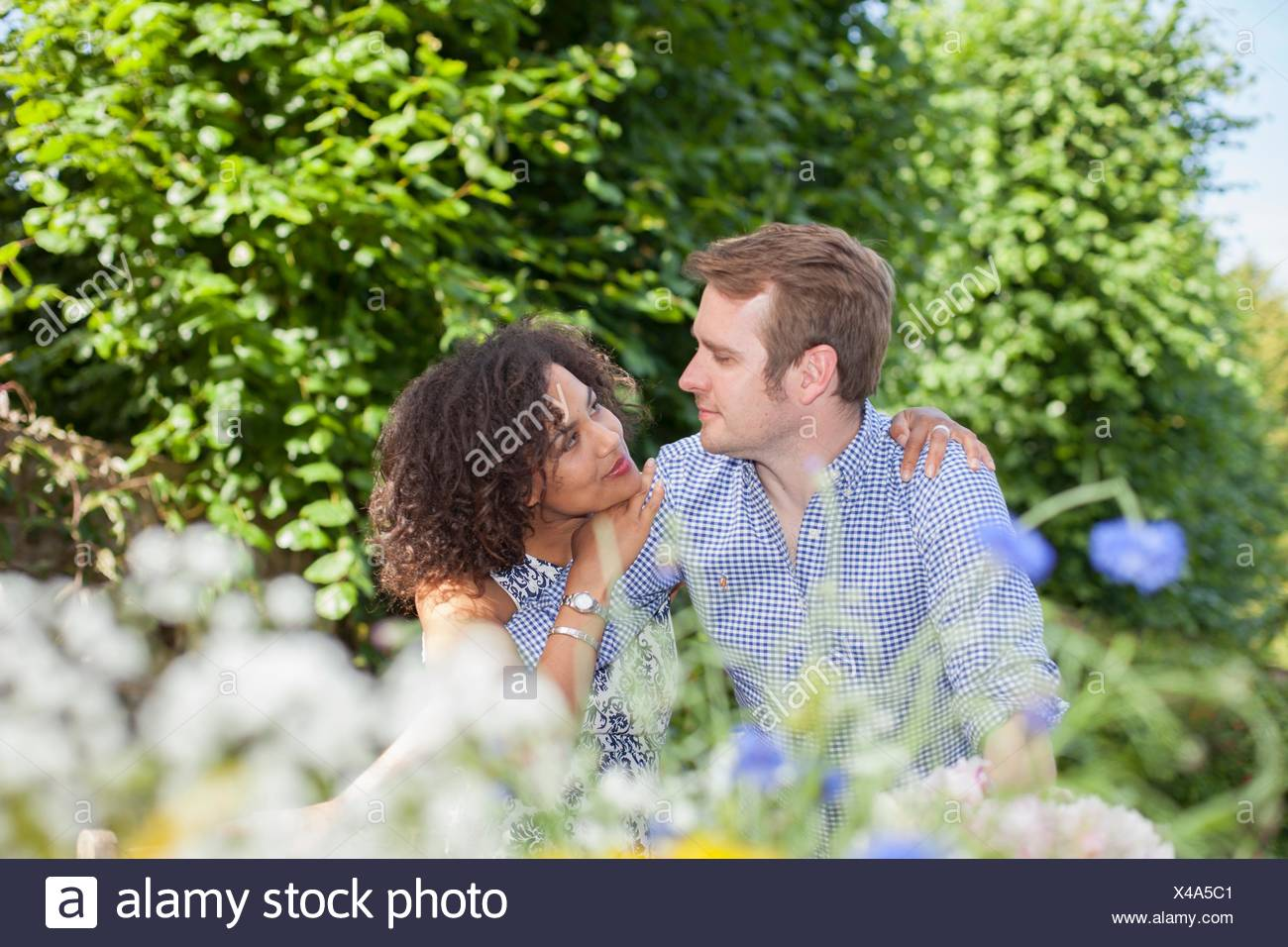 Mid adult couple, embracing, sitting face to face, outdoors - Stock Image