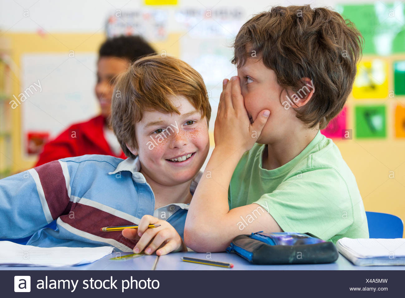 Primary schoolboys whispering in classroom - Stock Image