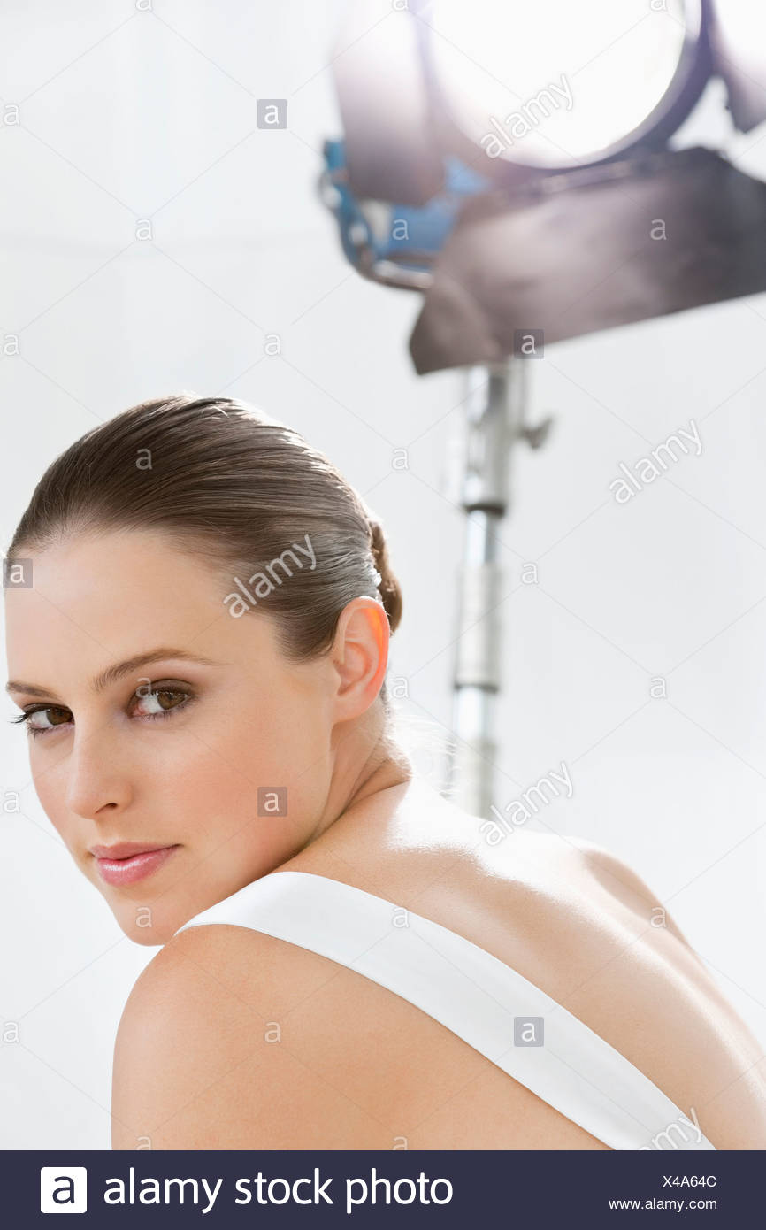 Portrait of smiling woman under spotlight - Stock Image