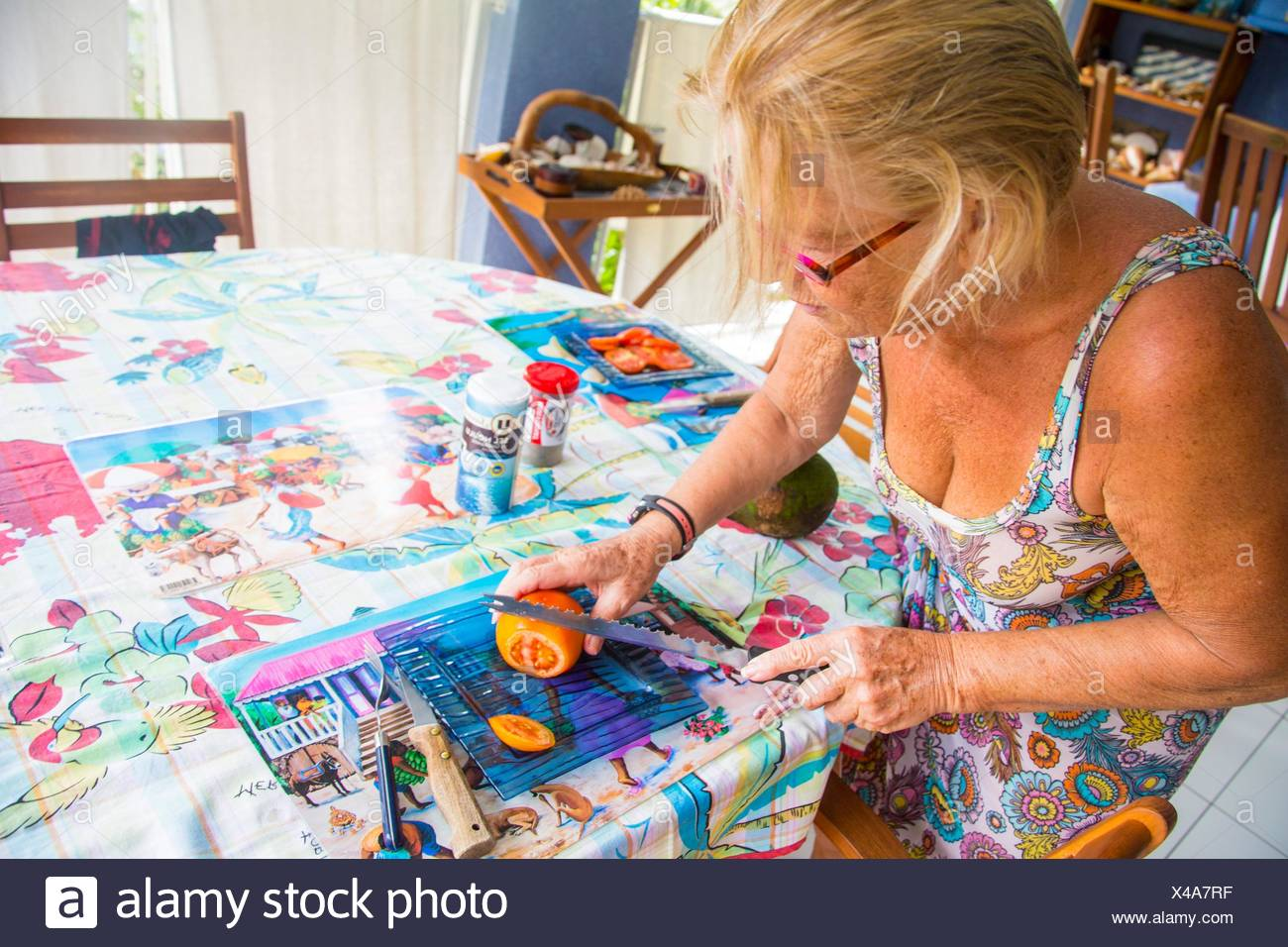 Older senior caucasian retired woman cooking lunch in her house in the Caribbean. She is cutting and slicing a tomato on a blue plate. - Stock Image