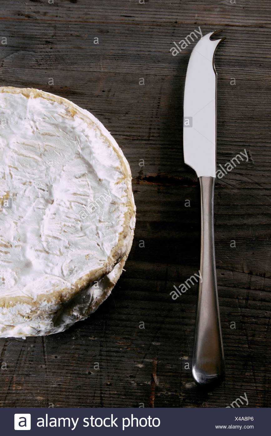 Camembert with a cheese knife on a rustic wooden surface - Stock Image