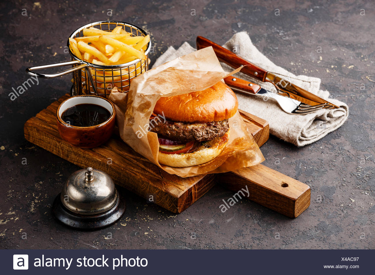 Burger with meat and French fries in basket on dark background and desk bell - Stock Image
