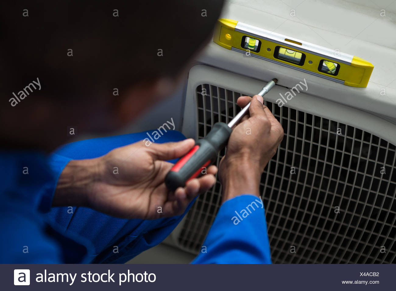 Handyman testing air conditioner with screwdriver Stock Photo