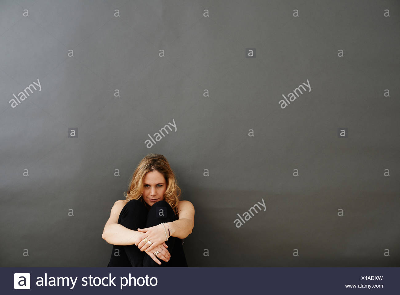 Mid adult woman sitting hugging knees to chest - Stock Image