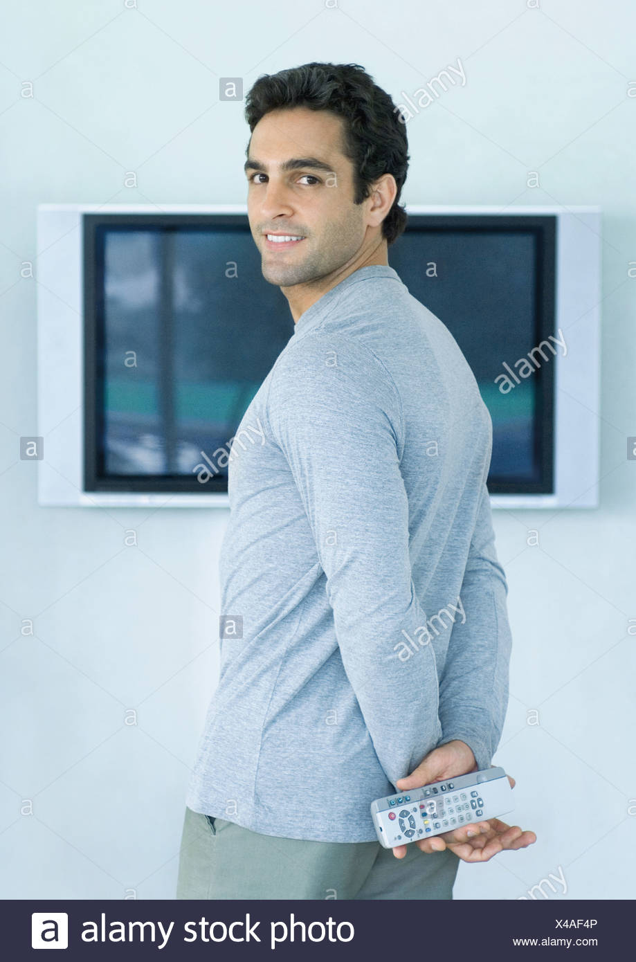 Man standing in front of widescreen TV, holding two remote controls, smiling over shoulder at camera - Stock Image