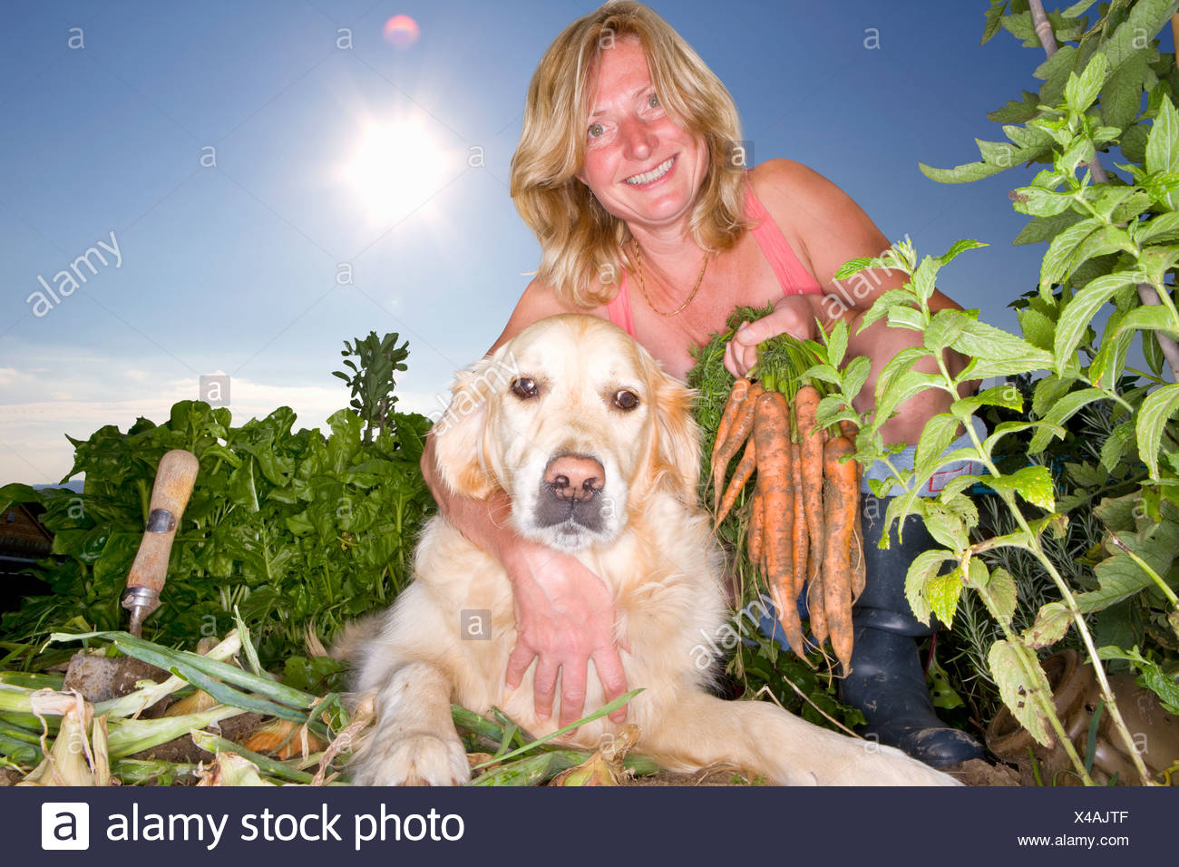 Portrait of woman and dog in vegetable garden Stock Photo