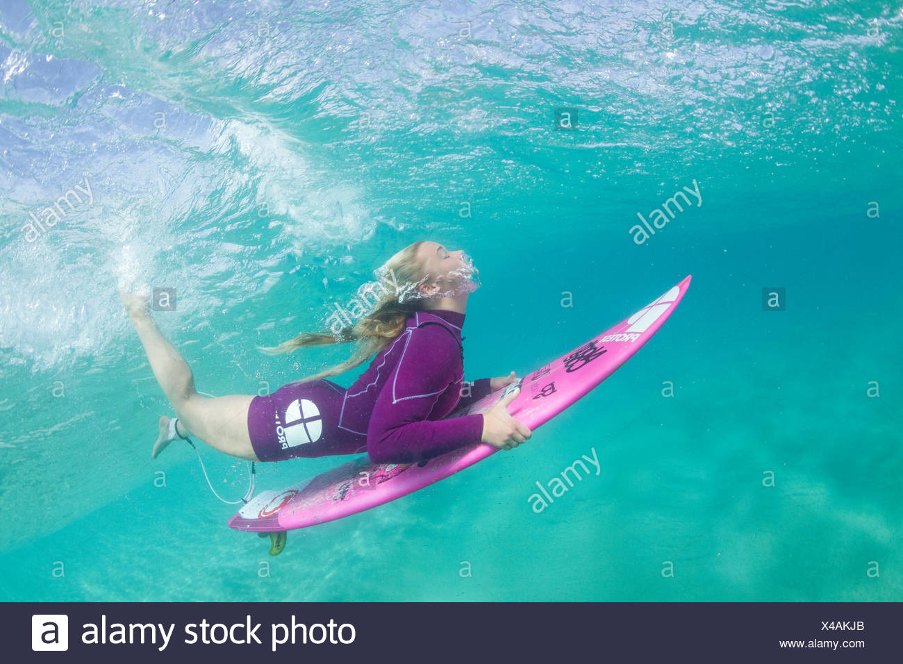 Underwater photo of a blonde surfer girl with a short wetsuit duck diving under a wave Stock Photo