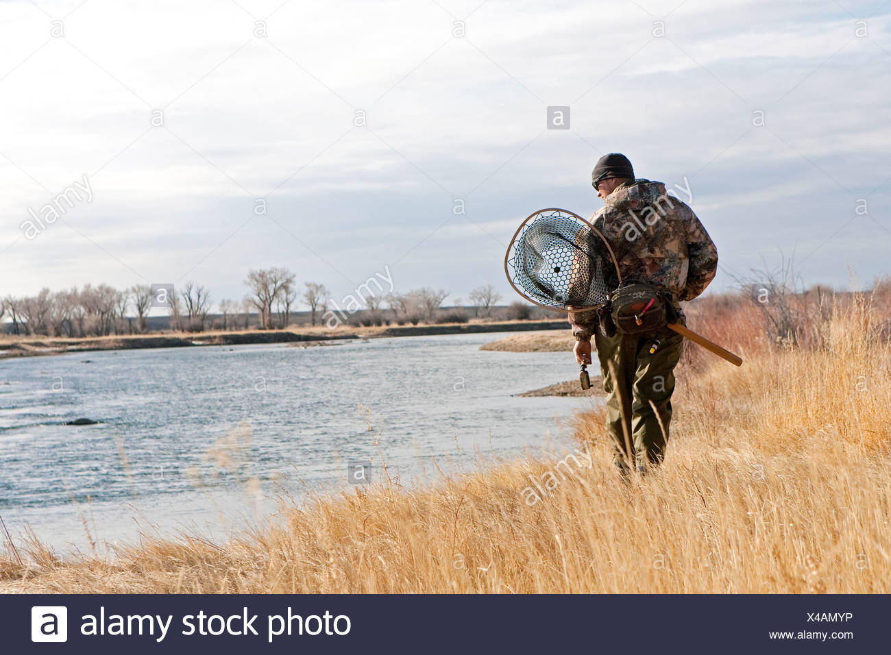 A man searches for trout while walking along a river. - Stock Image