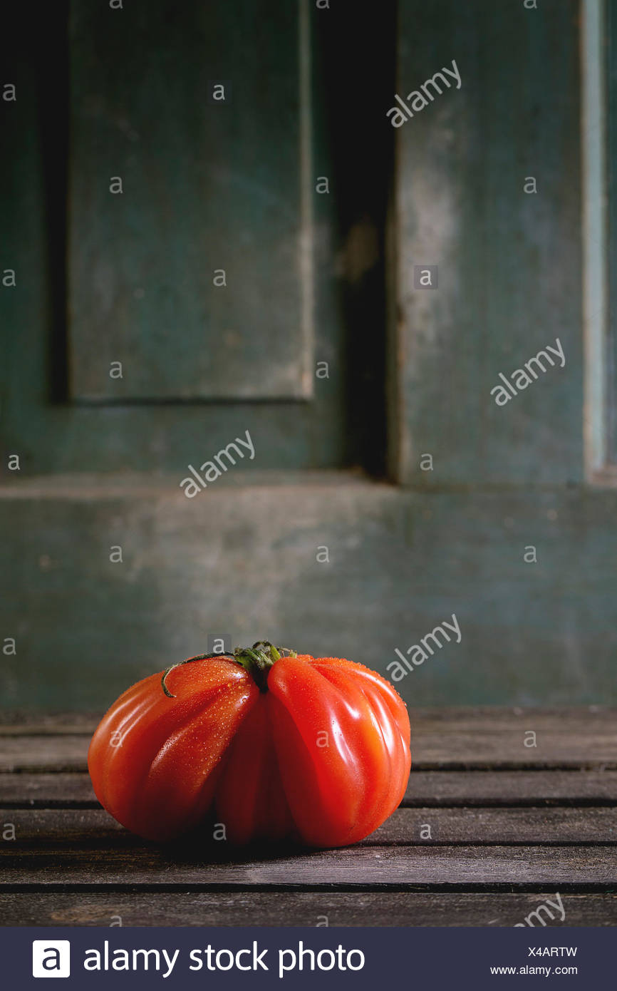 One big red tomato RAF over old wooden table. Dark rustic atmosphere - Stock Image