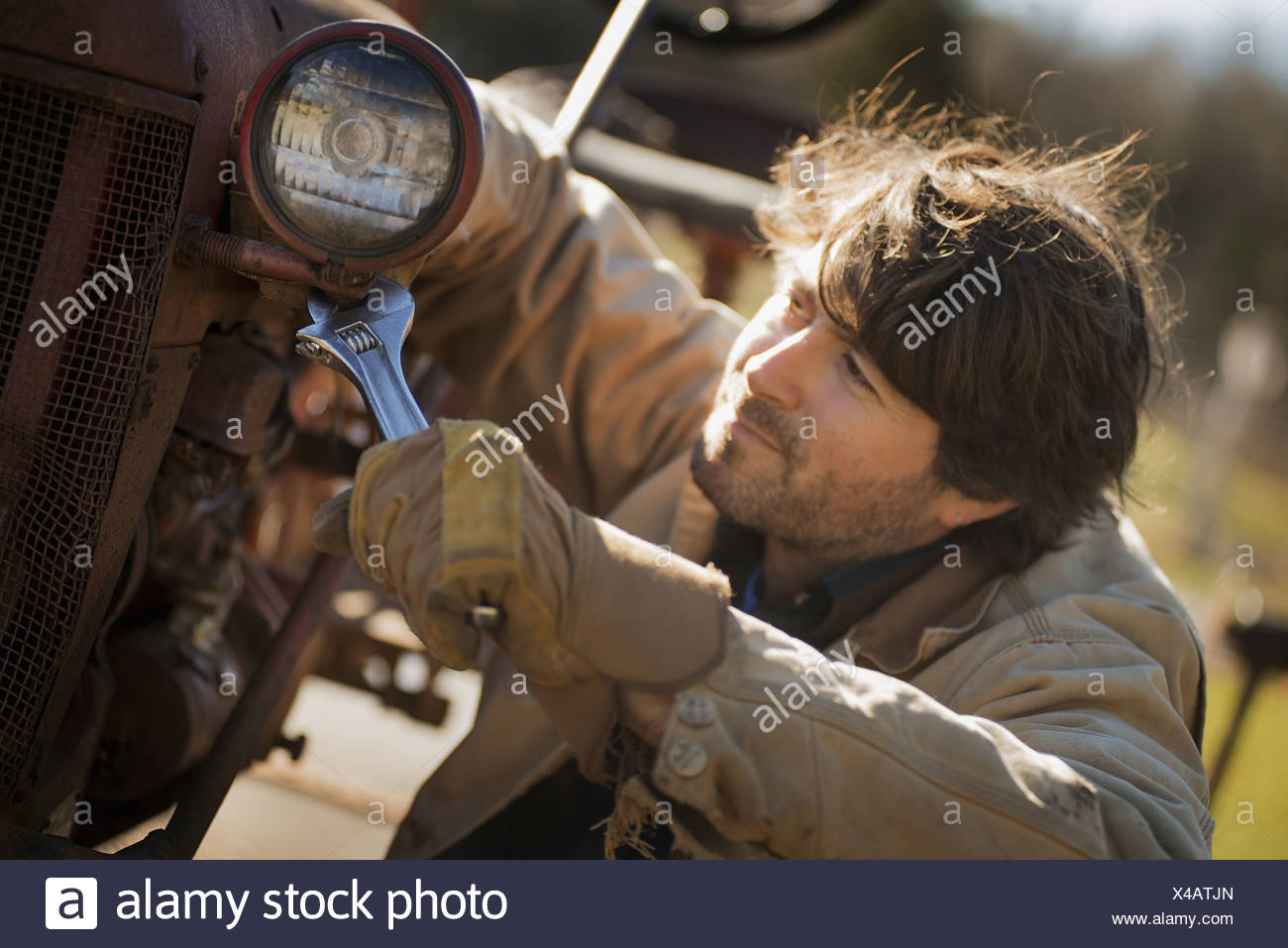 Working on an organic farm A man in a brown jacket using a spanner and working on farm machinery A tractor with a headlight - Stock Image