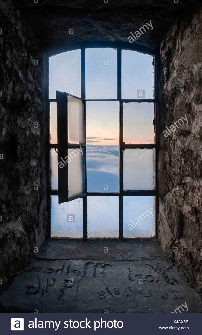 View of sunset over the clouds through tower windows by stonewalls at Norway - Stock Image