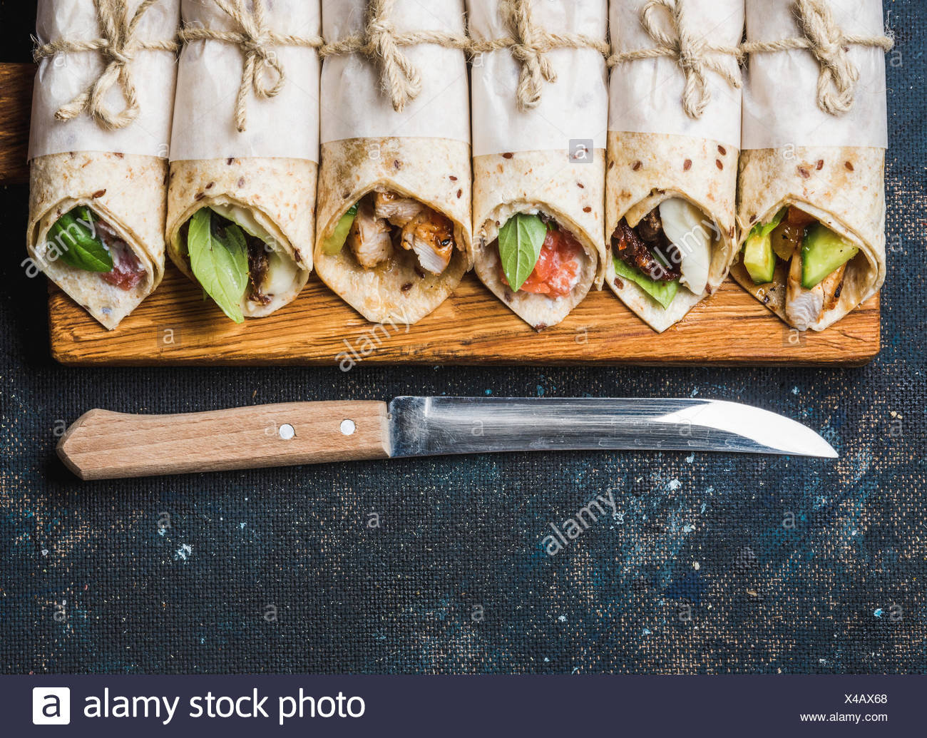 Tortilla wraps with various fillings on rustic wooden board and knife over dark blue painted plywood background, top view, copy - Stock Image