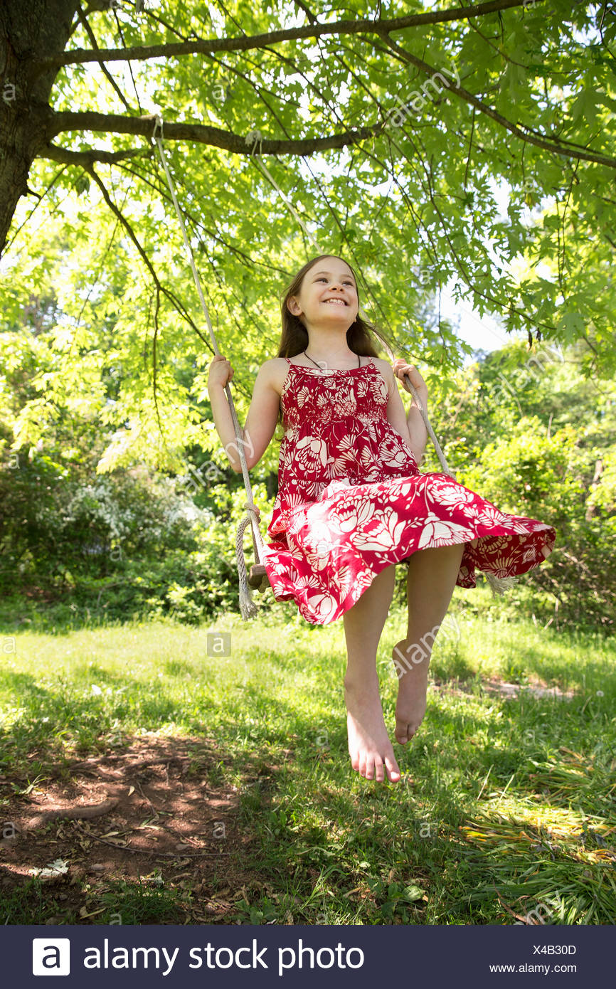 Summer. A girl in a sundress on a swing swinging from the bough of a leafy tree. Stock Photo