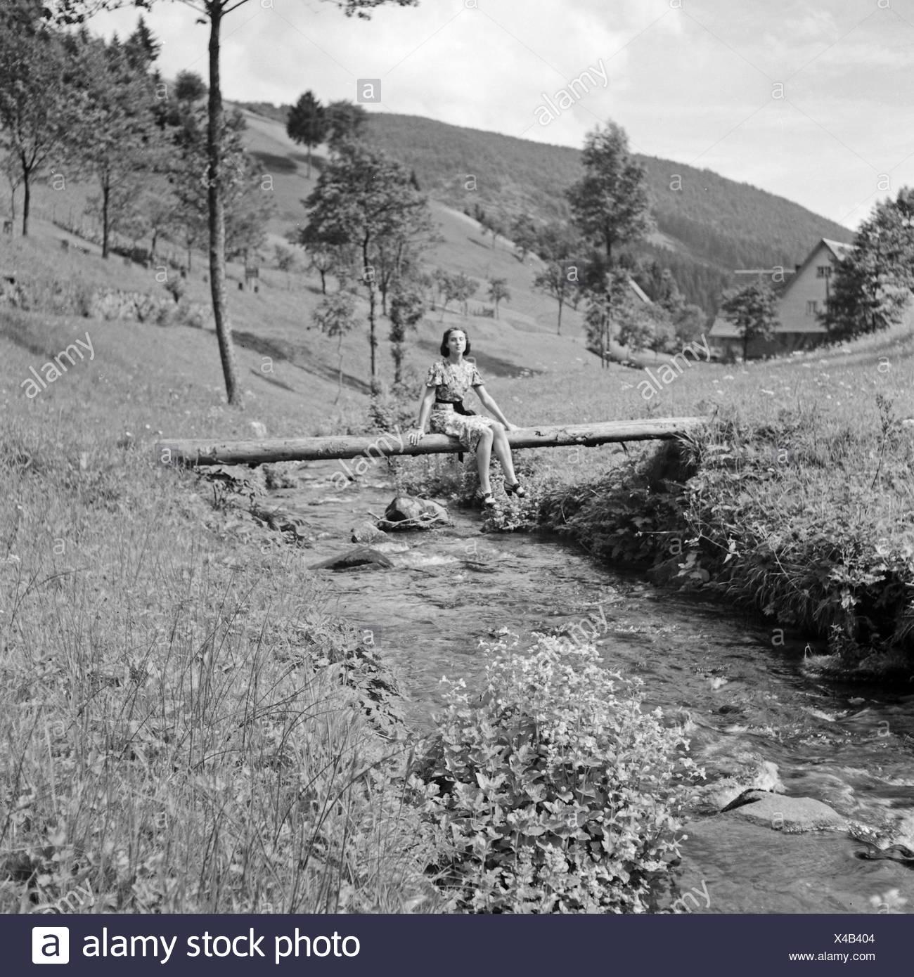 Eine junge Frau überquert einen Bach im Schwarzwald, Deutschland 1930er Jahre. A young woman crossing a creek in the Black Forest area, Germany 1930s. Stock Photo