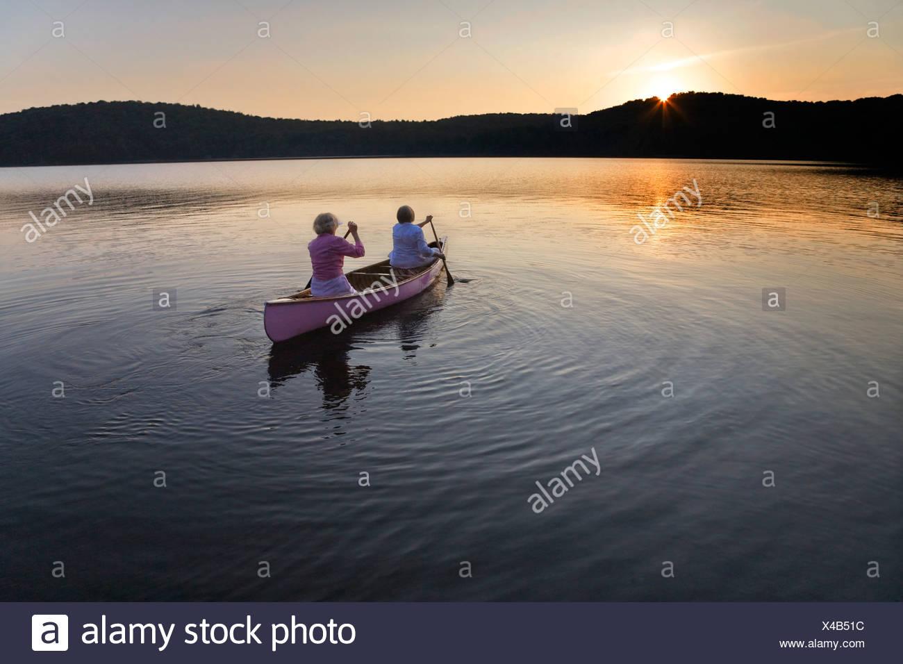Paddling toward the sunset, Smoke Lake, Algonquin Park, Ontario - Stock Image