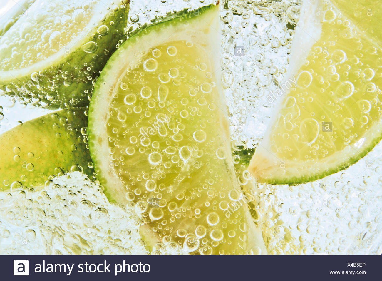 Lime slices in a fizzy drink, close-up - Stock Image