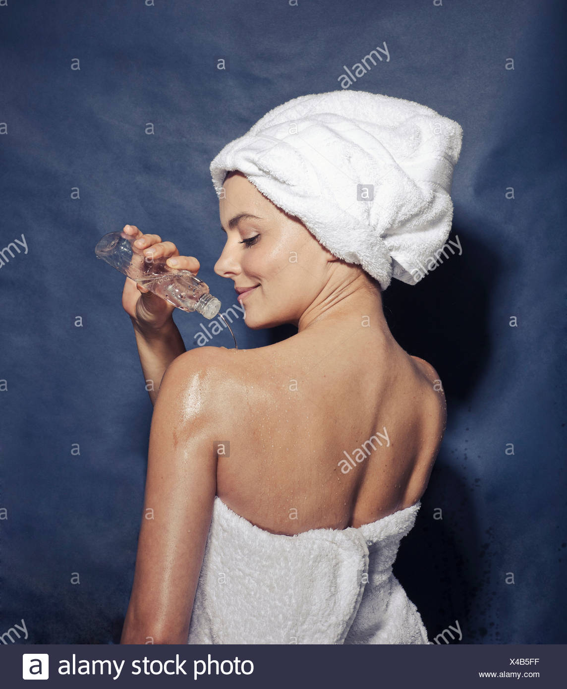 Young female applying body lotion to shoulder - Stock Image
