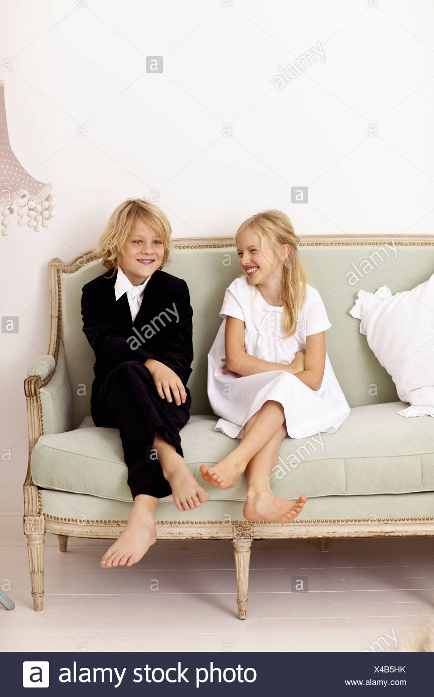 Siblings sitting on couch together - Stock Image
