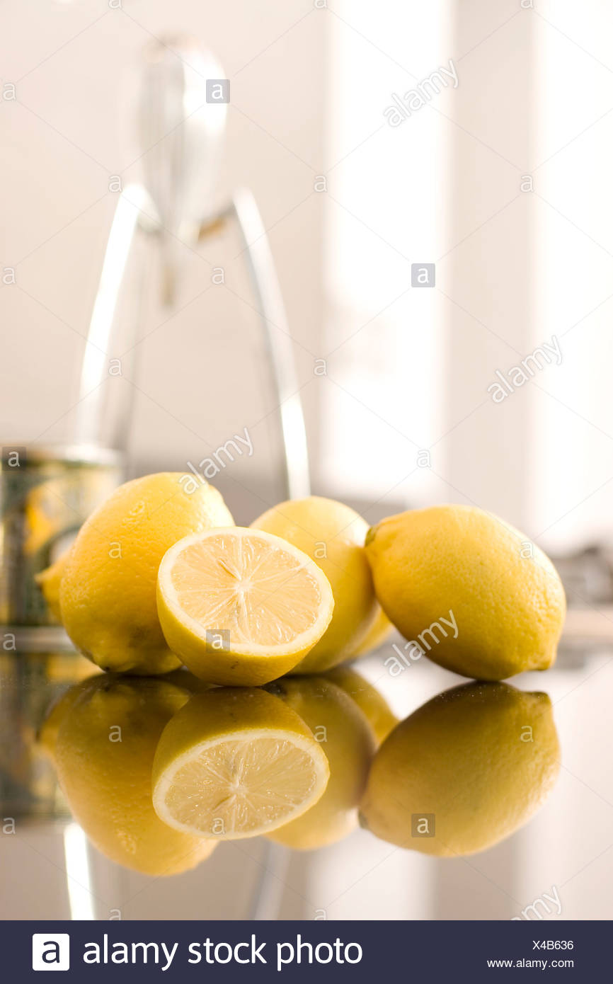 Lemons and an Alessi Juicy Salif Juicer by Philippe Starck in the background - Stock Image