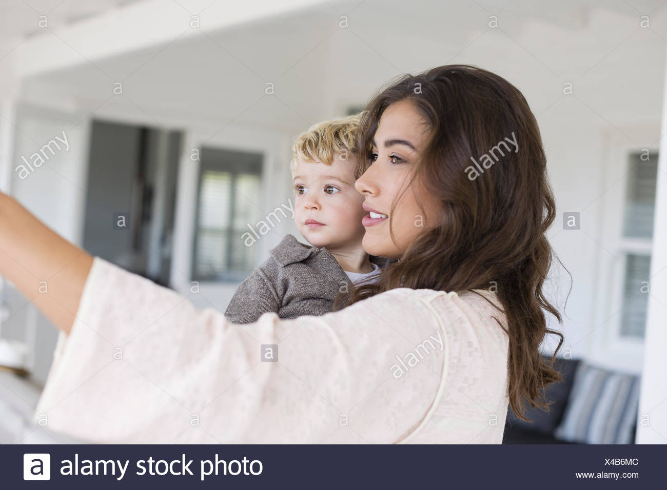 Beautiful mother and cute son taking selfie at home - Stock Image