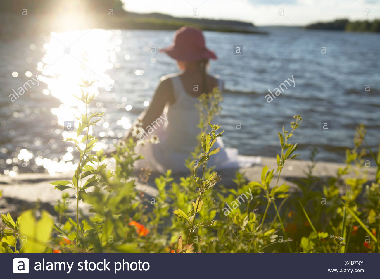 A woman on a cliff by shimmering water rear view. - Stock Image