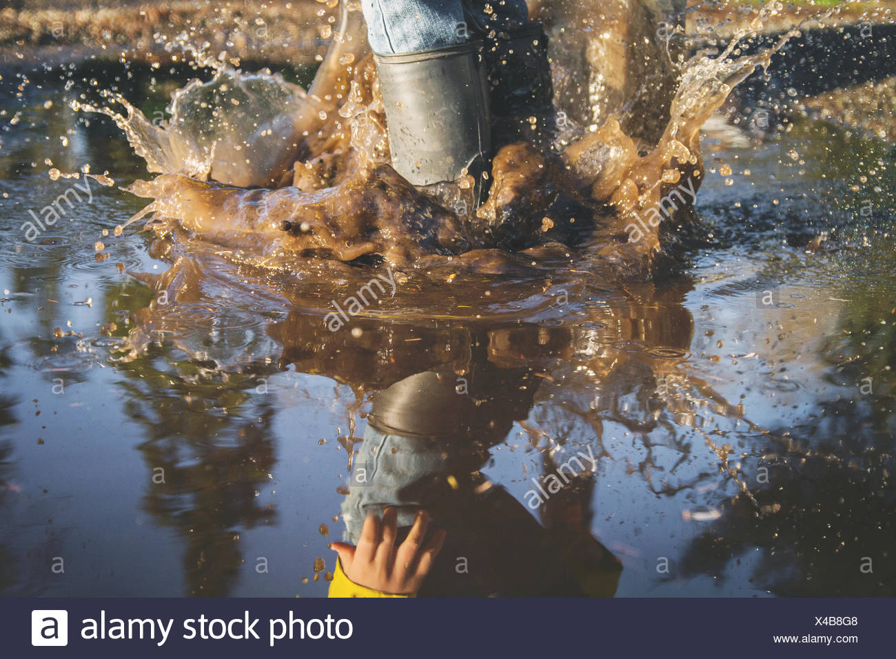 Close-up of child's legs splashing in a puddle of water Stock Photo