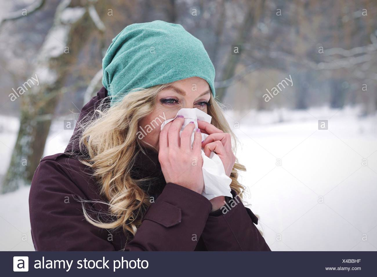 Woman Blowing Nose During Winter - Stock Image