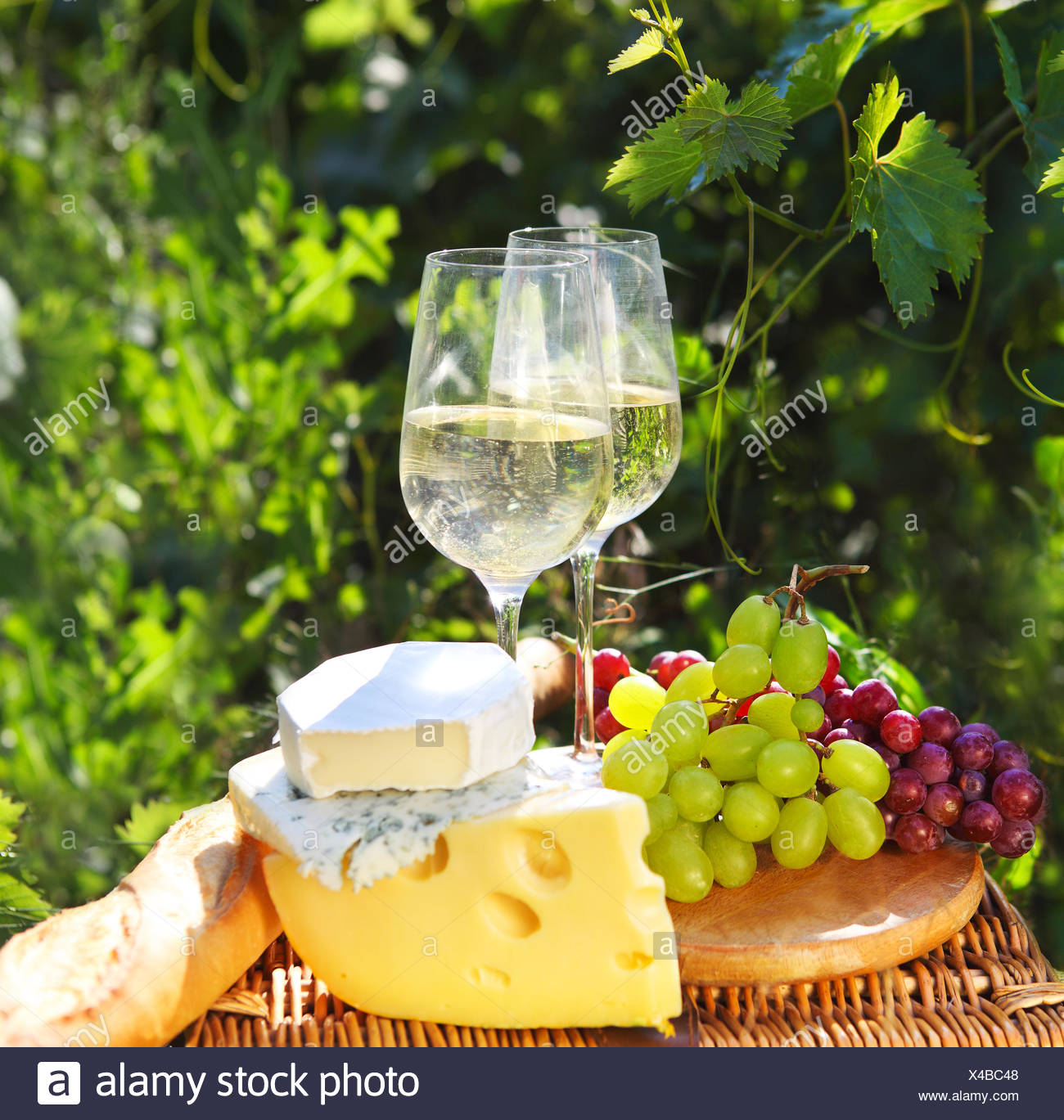 Various sorts of cheese, bread, grapes and two glasses of the white wine - Stock Image
