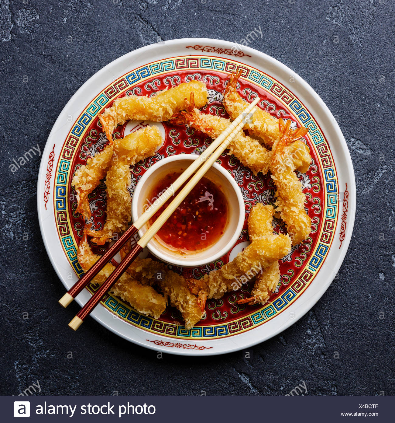 Deep fried breaded Tempura prawn shrimps with sauce on black stone background - Stock Image