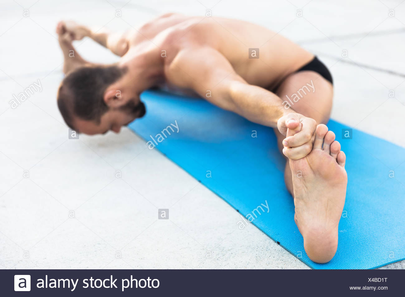 Man practicing yoga, sitting on yoga mat doing the splits and touching toes - Stock Image