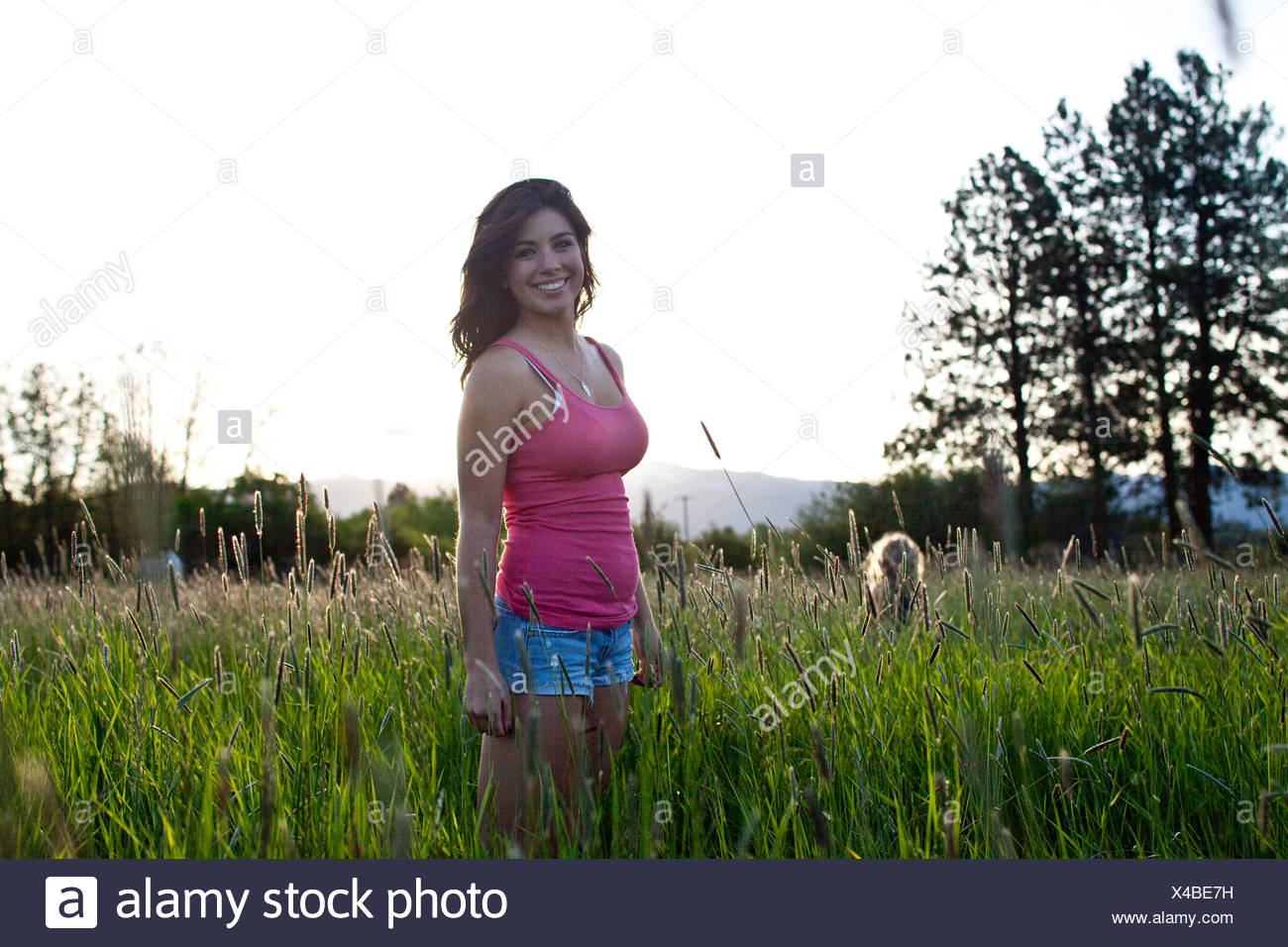 A girl stands in tall grass on a sunny day in Idaho. - Stock Image