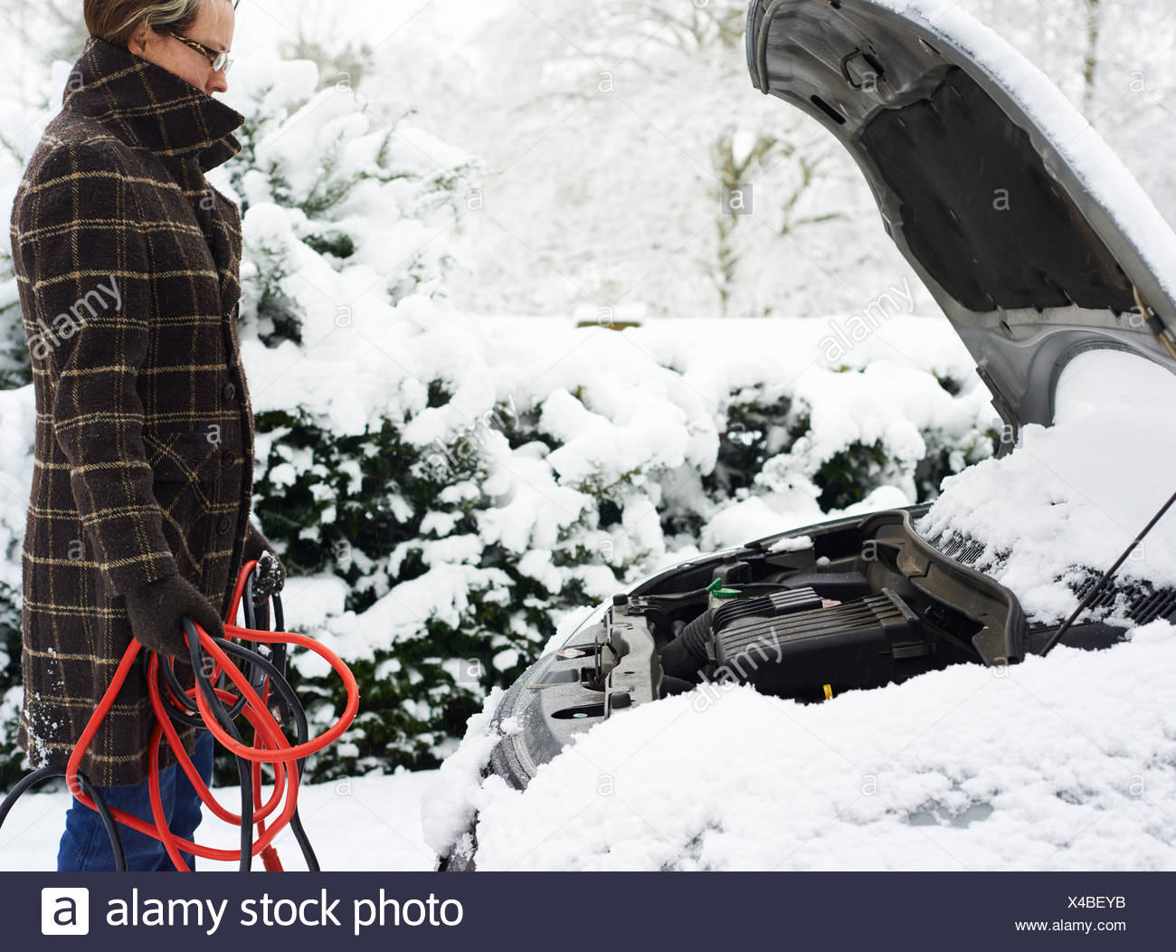 Woman working on broken down car in snow - Stock Image