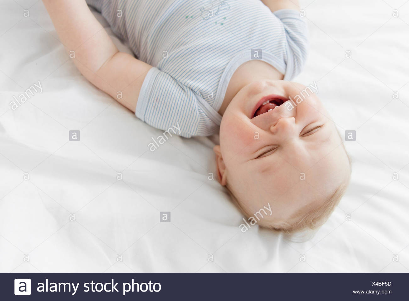High angle view of baby boy with blond hair lying on a bed. - Stock Image