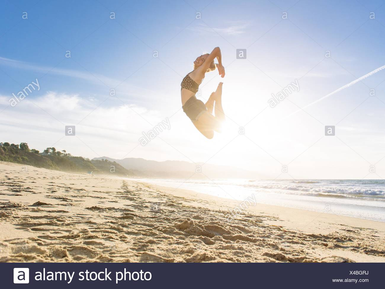 Young woman on beach, leaping in air, sunset - Stock Image