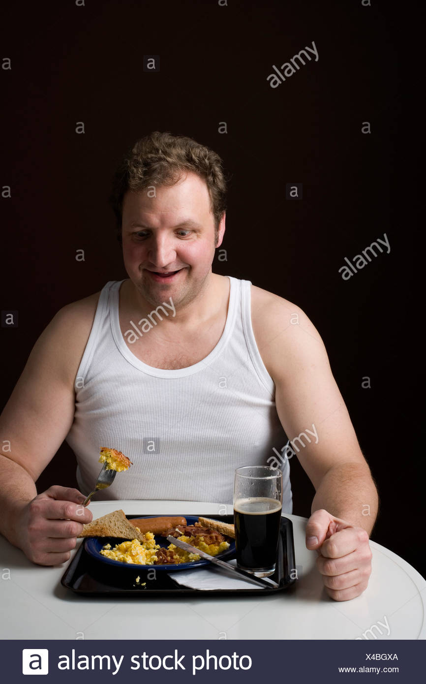 Stereotypical Englishman eating an English breakfast - Stock Image