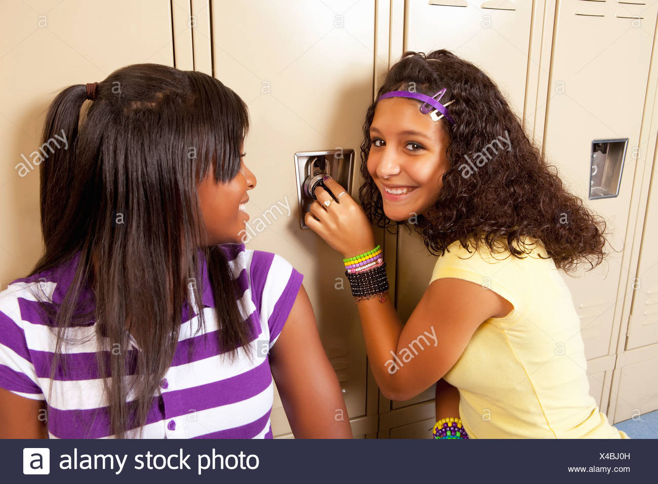 Fort Lauderdale, Florida, United States Of America; Two Teenage Girls Sitting In Hallway Doing The Combination Lock On A Locker - Stock Image