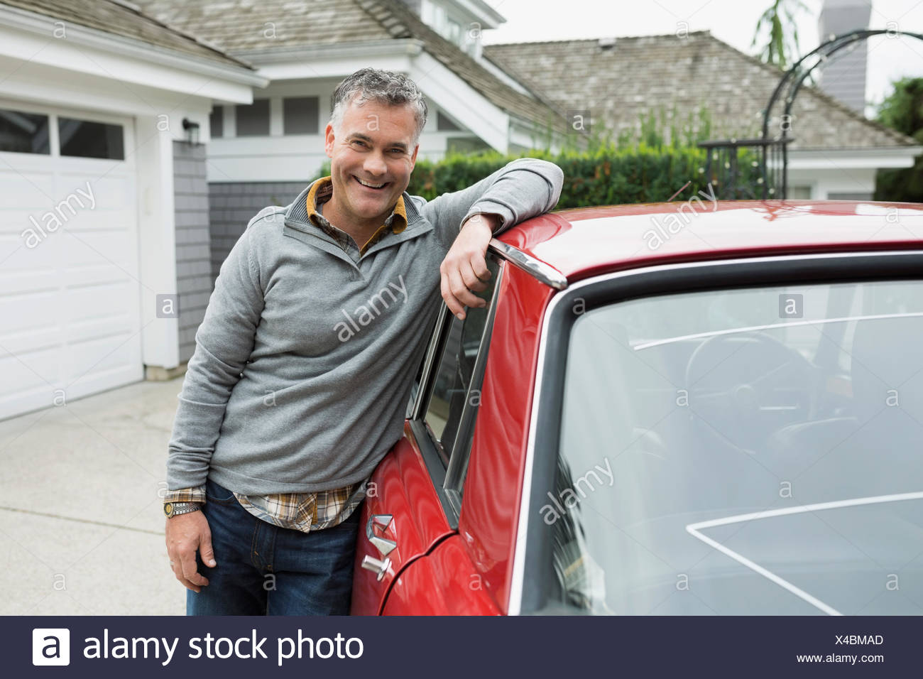 Portrait smiling man leaning classic car in driveway - Stock Image
