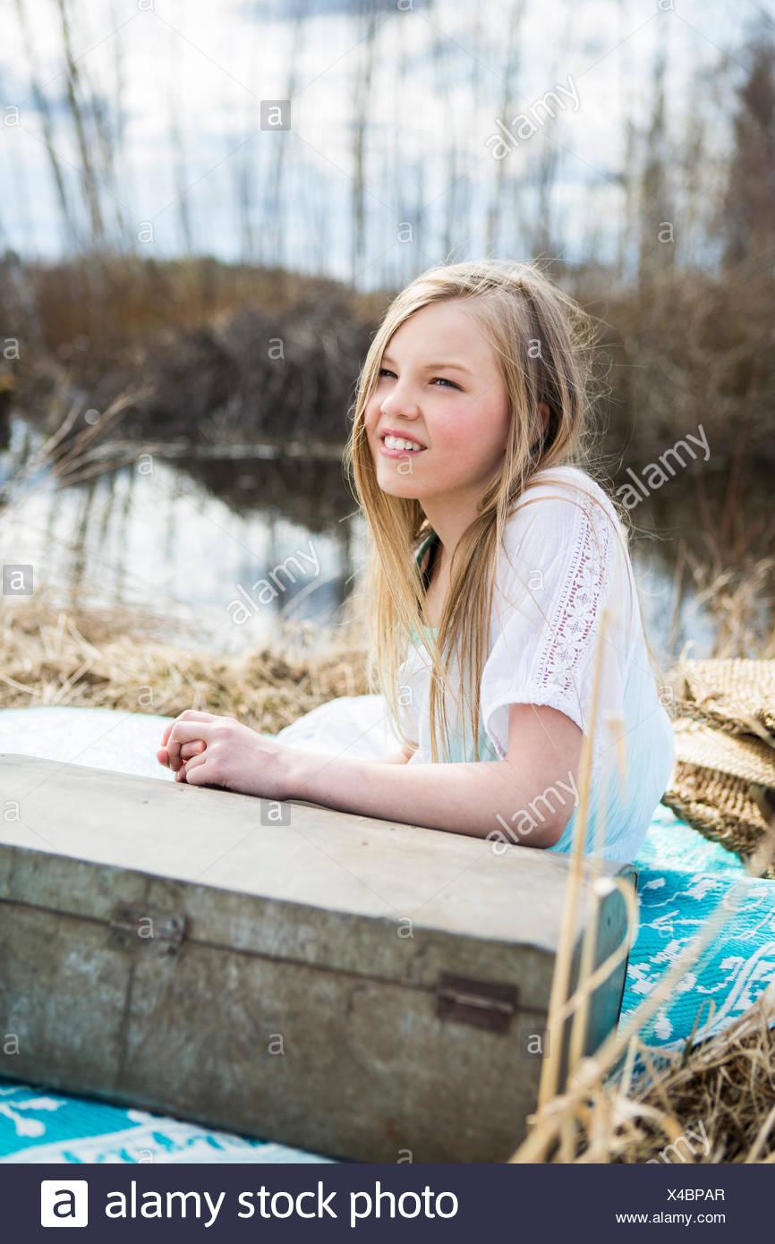Finland, Keski-Suomi, Aanekoski, Smiling girl (12-13) sitting on blanket outdoor - Stock Image