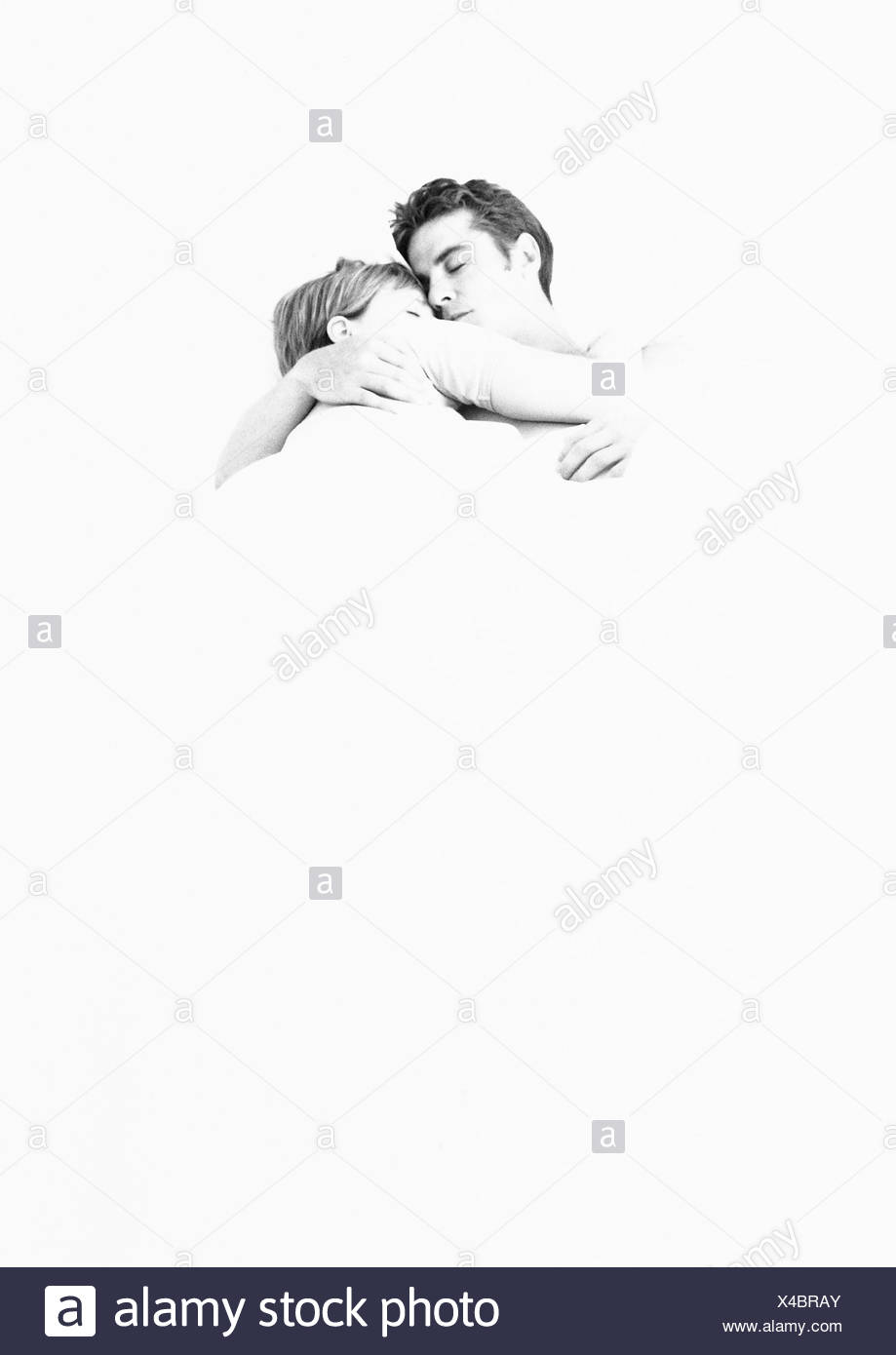 Couple lying in each other's arms, b&w - Stock Image