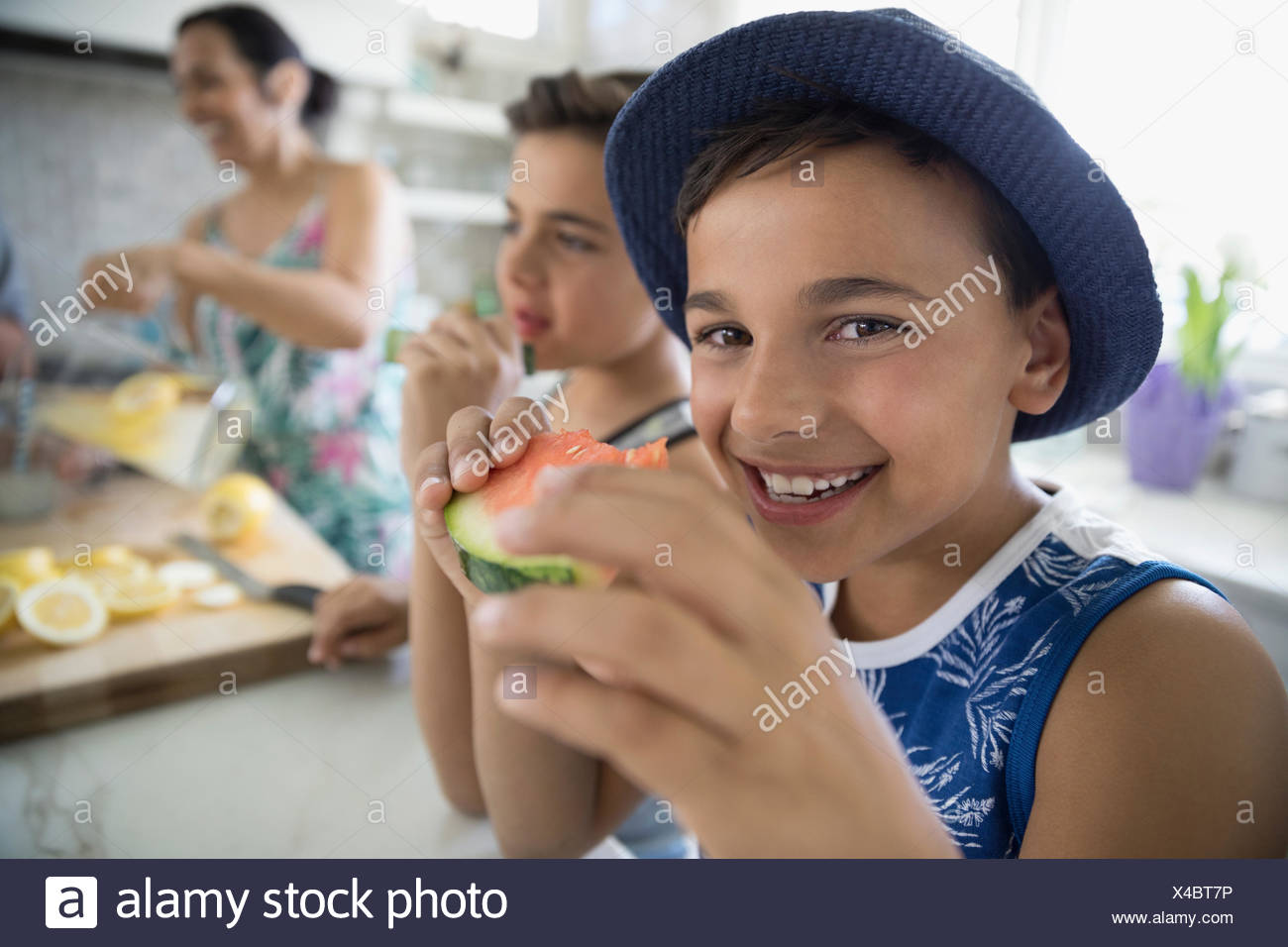 Portrait smiling boy eating watermelon in kitchen - Stock Image