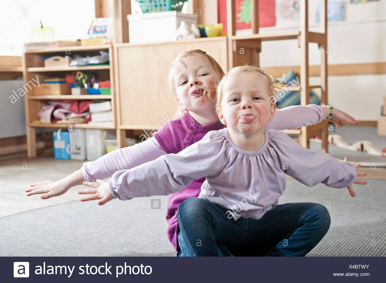 Portrait of two little sisters in kindergarten sticking out tongues - Stock Image