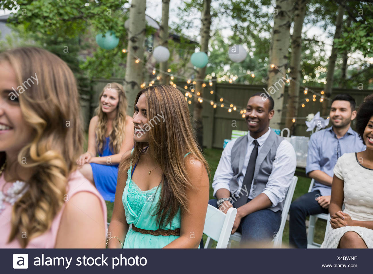 Smiling wedding guests enjoying backyard wedding - Stock Image