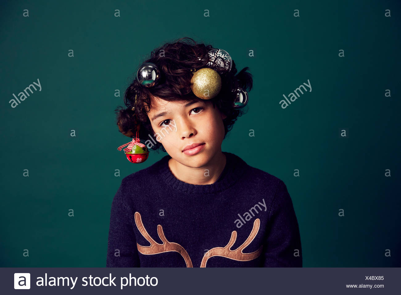 88358fa41b7 Portrait of teenage boy wearing Christmas jumper, and baubles in ...