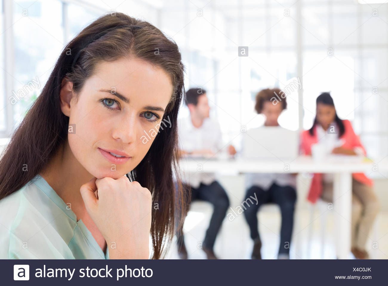 Attractive office worker thinking and looking at camera - Stock Image